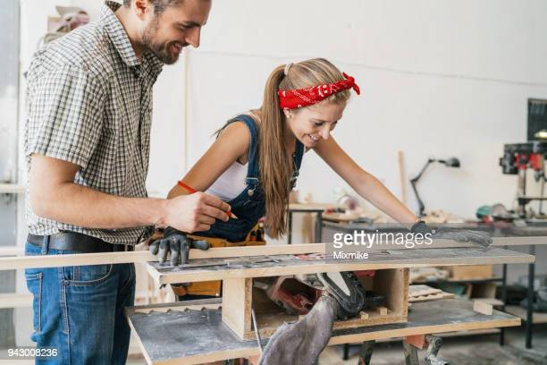 frau zimmermann schleifen holzbohle auf schreinerei - unterschicht stereotypen stock-fotos und bilder