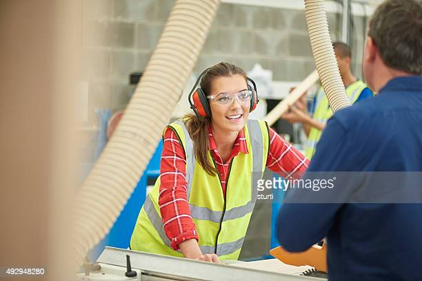 female carpenter in the woodshop listening to her boss