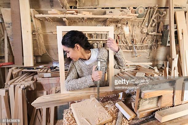 Female carpenter in wooden frame