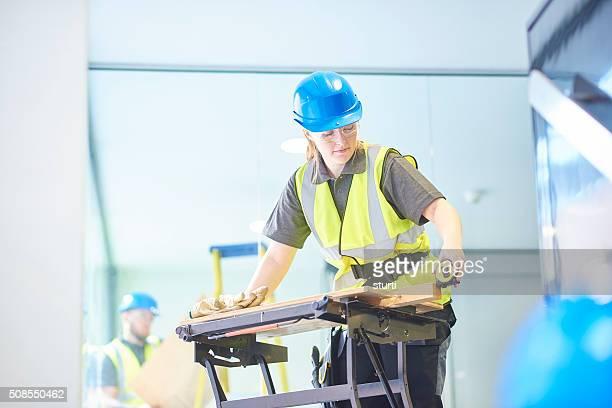 female carpenter is measuring up