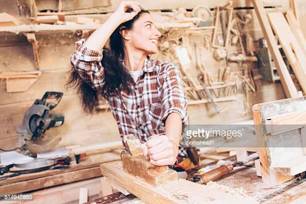 Weibliche Tischler Planung Holz mit einem Hobel bei der Arbeit Website