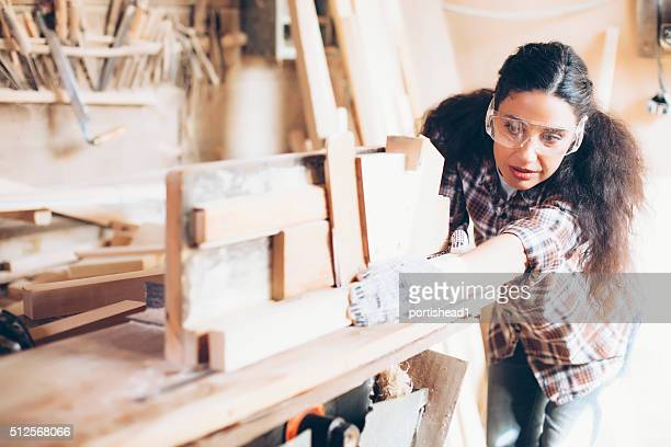 Female carpenter planing wood with at work site