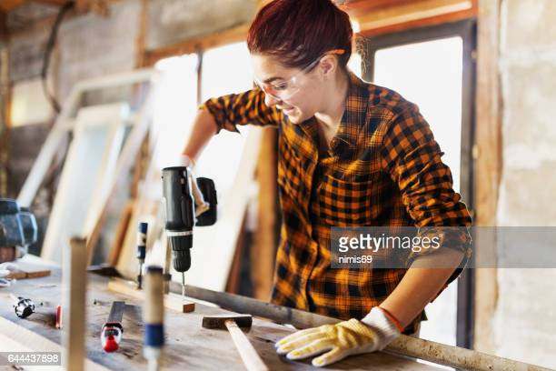 Female carpenter screwing her work together