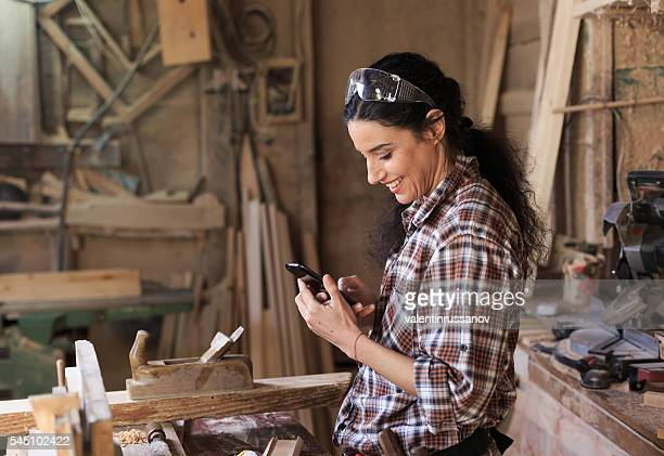 Female carpenter using a phone at workhop