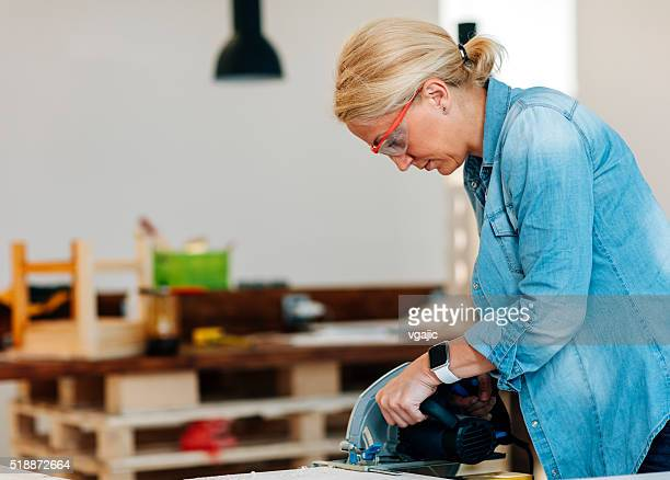 Female Carpenter Using Circular Saw.