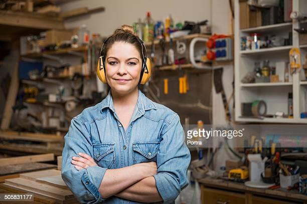 Female carpenter wearing her yellow earmuffs.