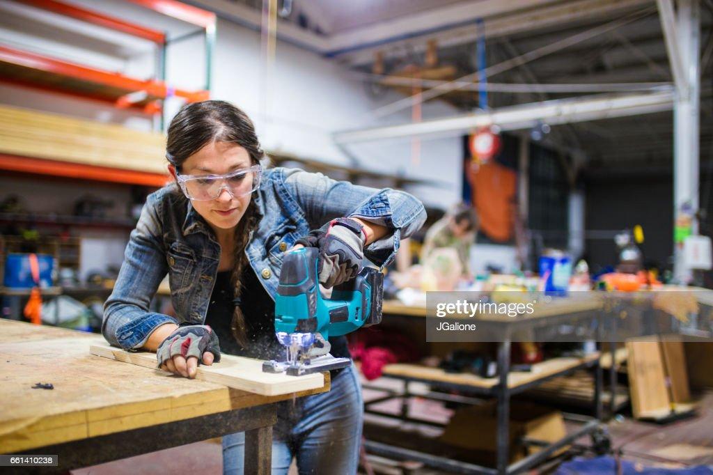 Female carpenter working in a workshop : Stock Photo