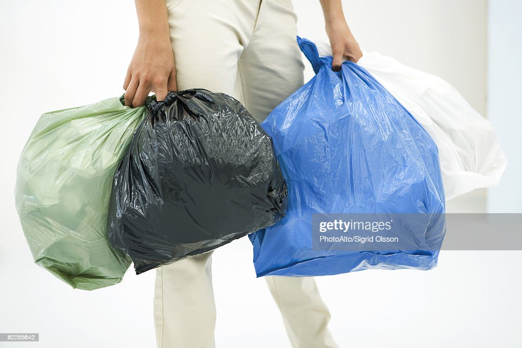 Female carrying several bags of garbage, cropped view : Stock Photo