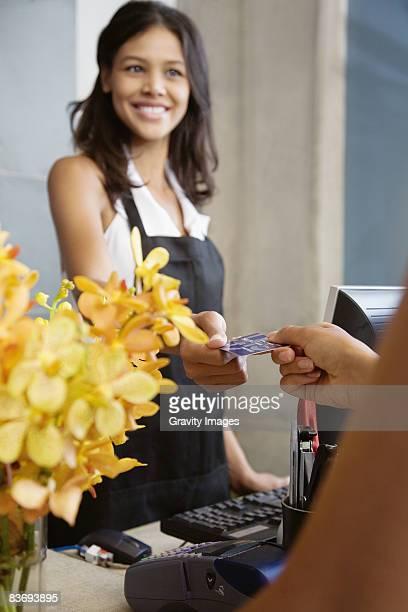 Female cashier hands customer credit card