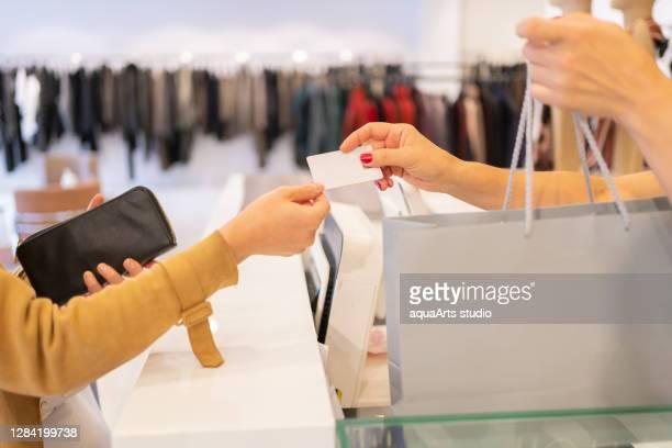 de vrouwelijke kassier geeft creditcard en het winkelen zak aan een vrouwenklant bij kledingopslag - friday stockfoto's en -beelden