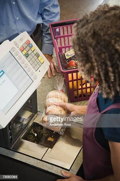 Female cashier scanning groceries, elevated view