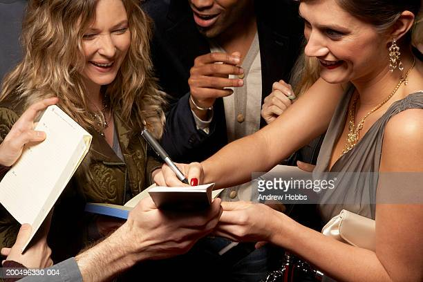 Female celebrity in evening dress signing autographs for fans at event