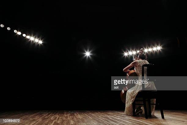 a female cellist playing cello on stage, rear view - performing arts event stock pictures, royalty-free photos & images