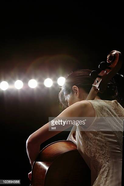 A female cellist playing cello on stage,close up.