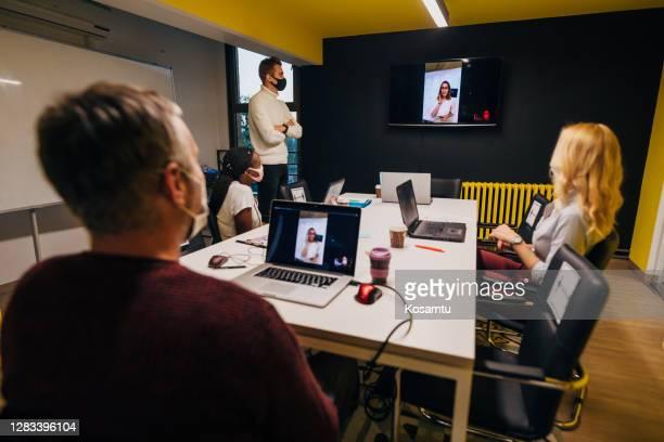 彼女のチームが役員室で彼女のプレゼンテーションを聞いている間、ビデオ会議をリードする女性ceo - insight tv ストックフォトと画像