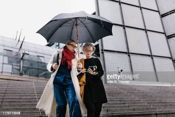female ceo walking outdoors with assistant - yellow coat stock pictures, royalty-free photos & images