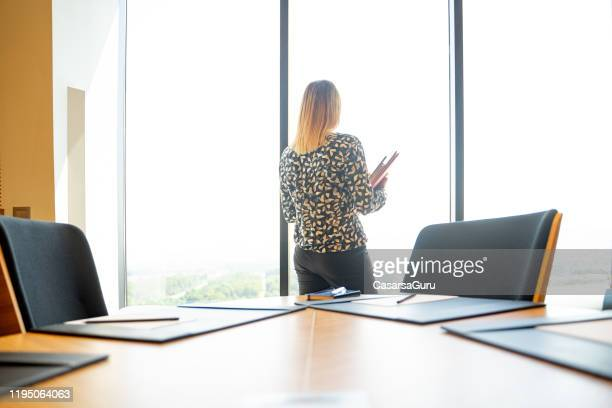 female ceo working after regular time in empty conference room - stock photo - vulnerability stock pictures, royalty-free photos & images