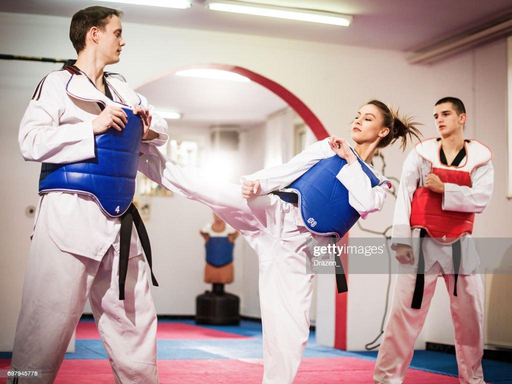 Female champion in taekwondo kicking on training : Stock Photo