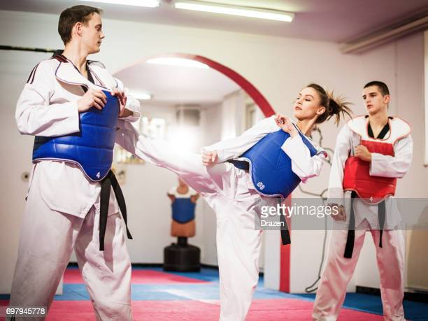 female champion in taekwondo kicking on training - artes marciais imagens e fotografias de stock