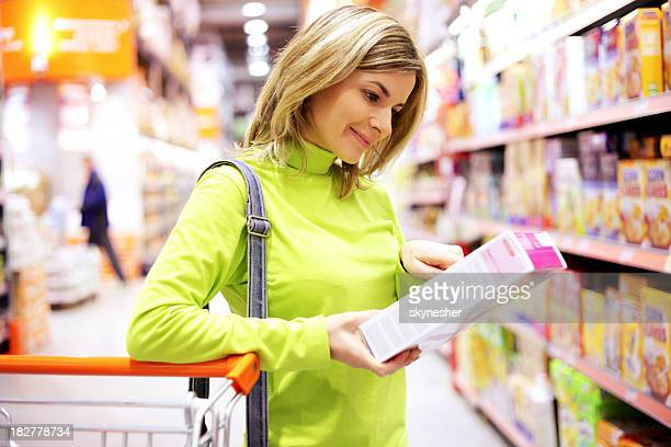 female checking food labeling in supermarket. - labeling stock photos and pictures