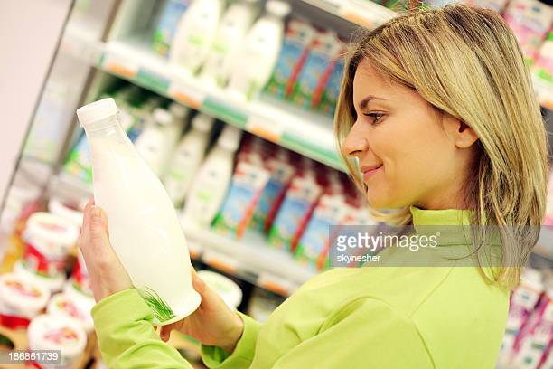 female checking milk's labeling in supermarket. - labeling stock pictures, royalty-free photos & images