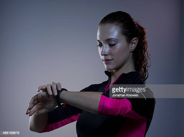 female checking watch after exercising - hair back stock pictures, royalty-free photos & images