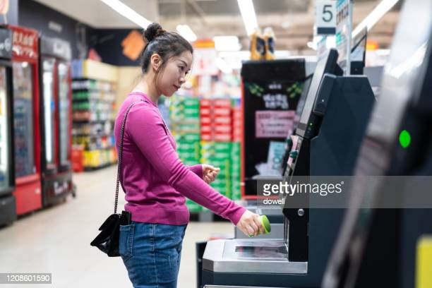 female checkout by automatic payment machine in supermarket - individuality stock pictures, royalty-free photos & images