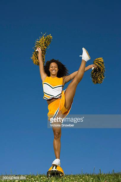 female cheerleader doing high kick on football helmet - cheerleader high kick stock photos and pictures