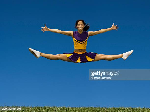 female cheerleader doing jump splits in air - doing the splits stock photos and pictures