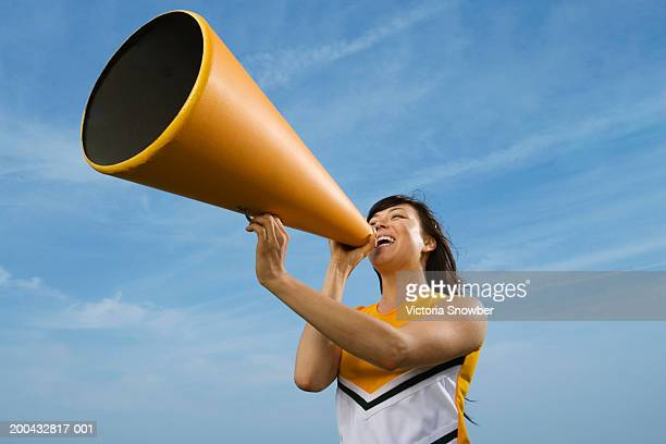 female cheerleader shouting into megaphone - asian cheerleaders stock photos and pictures