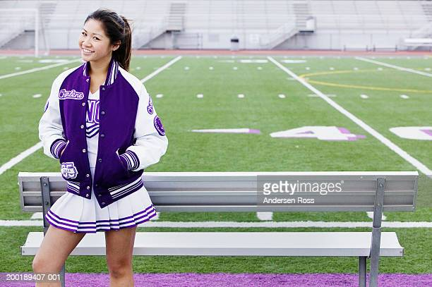 female cheerleader (16-18) standing near football field, portrait - asian cheerleaders stock photos and pictures