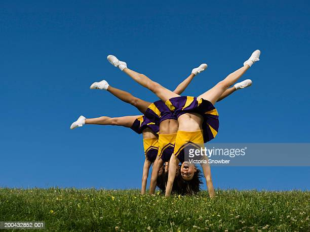 female cheerleaders doing handstands - asian cheerleaders stock photos and pictures