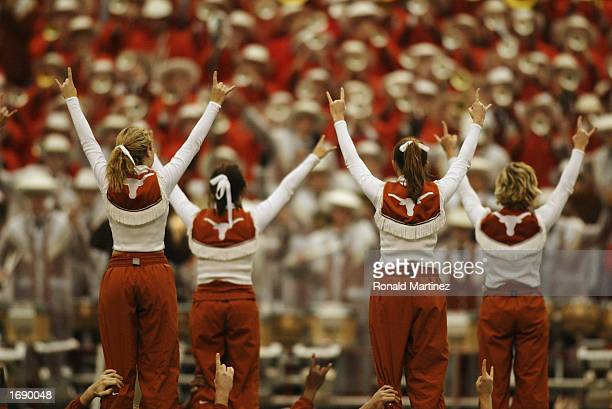"""Female cheerleaders of the Texas Longhorns stand on the shoulders of male cheerleaders and flash the """"Hook 'Em Horns"""" sign after the victory over the..."""
