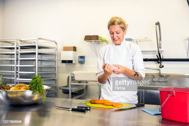 a female chef accidentally cuts her finger in a commercial kitchen while preparing food. - wounded stock pictures, royalty-free photos & images