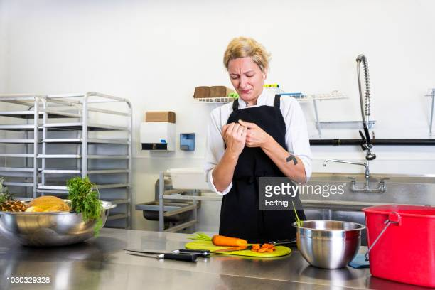 a female chef accidentally cuts her finger in a commercial kitchen while preparing food. - finger injury stock pictures, royalty-free photos & images