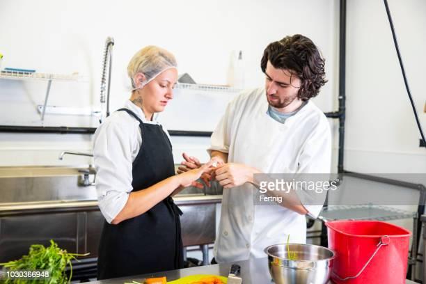 Un chef féminin coupe accidentellement son doigt dans une cuisine commerciale tout en préparant la nourriture.