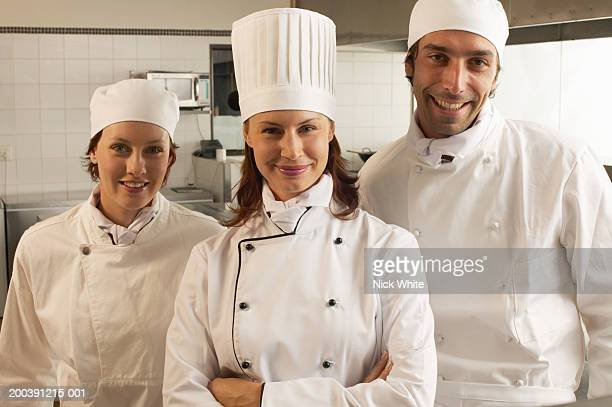female chef and two male and female cooks, smiling, portrait - chef's hat stock pictures, royalty-free photos & images