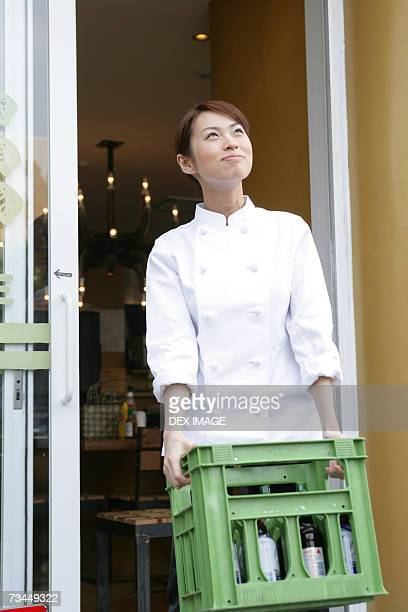 Female chef carrying a container
