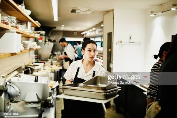 Female chef carrying stack of dirty pans though kitchen to be cleaned