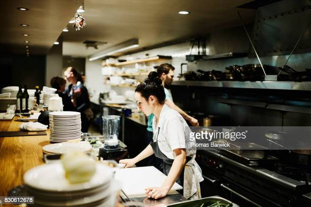 Female chef checking list while preparing for dinner service in restaurant