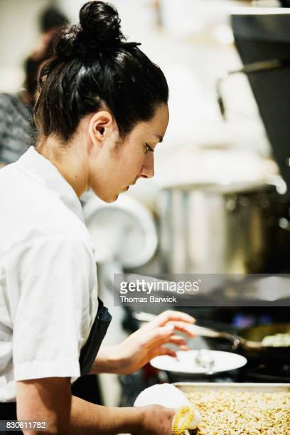 Female chef checking roasting pan while preparing for dinner service in restaurant kitchen