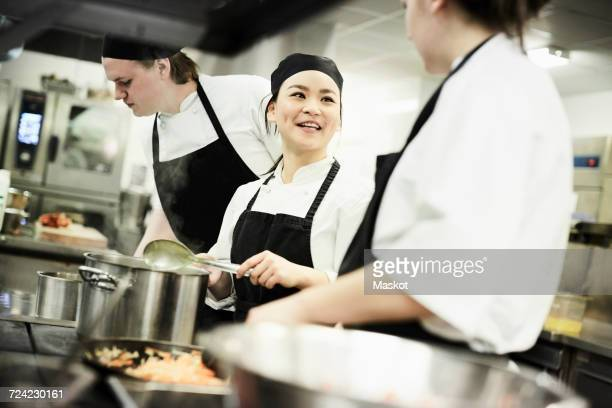 Female chef cooking food while talking with colleague in commercial kitchen