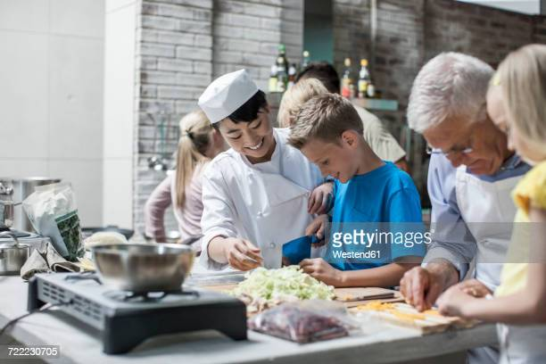 Female chef cooking with kids in cooking class