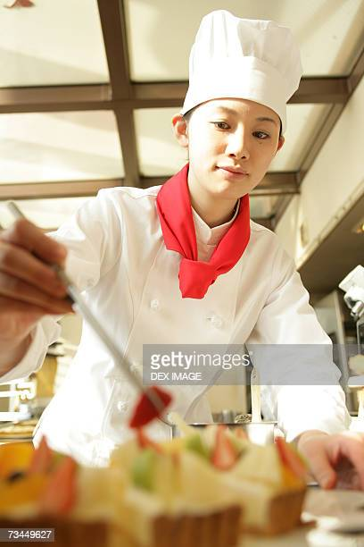 Female chef decorating a tart with a slice of strawberry