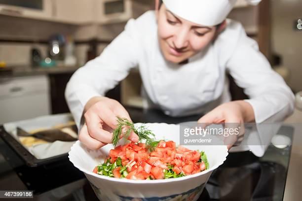 Femmina chef in cucina decorare piatto