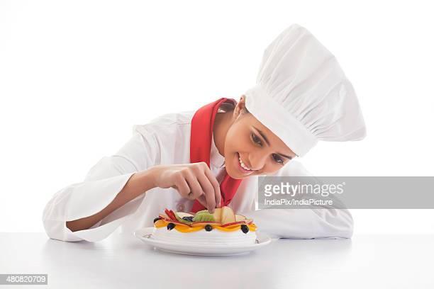 Female chef decorating fresh fruitcake over white background