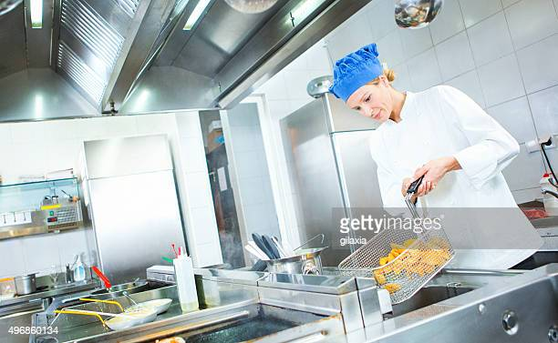 Female chef frying potatoes in restaurant kitchen.