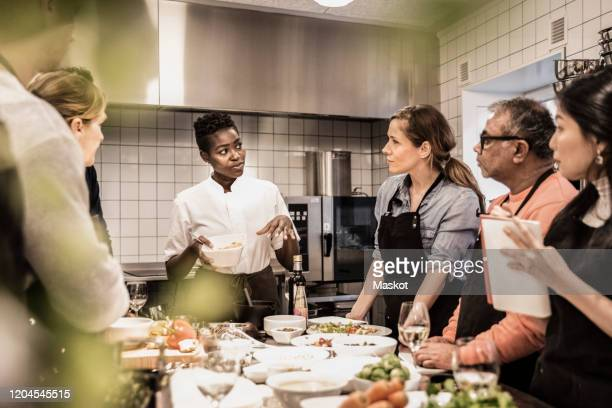 female chef giving instructions to adult students standing around table in cooking class - chef stock pictures, royalty-free photos & images