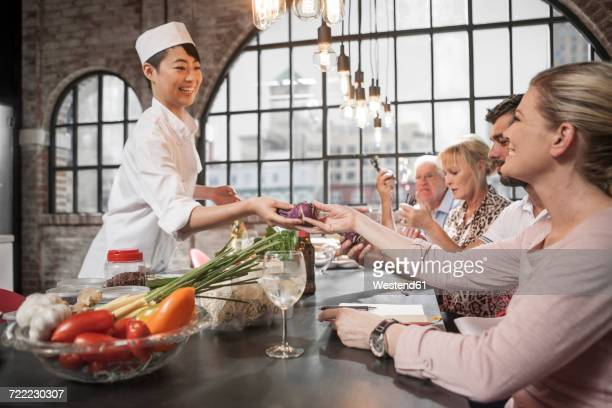 Female chef handing over beetroot to female student in cooking class