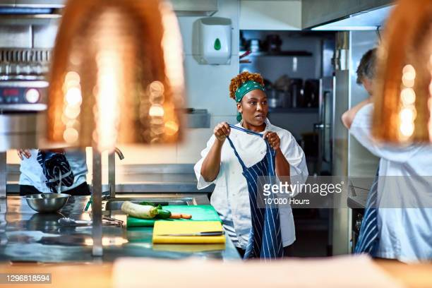 female chef holding apron in commercial kitchen - kitchen stock pictures, royalty-free photos & images